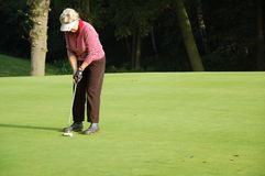 Female golfer putting Royalty Free Stock Photos