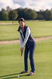 Female golfer putting on green. Attractive female golfer putting on the lush green golf course, looking at the camera with a healthy smile Stock Photography
