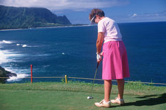 Female golfer putting in Hawaii Royalty Free Stock Image