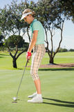 Female golfer putting her ball Royalty Free Stock Photo
