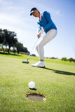 Female golfer putting her ball Stock Photography