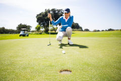 Female golfer putting her ball Stock Images