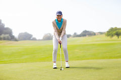 Female golfer putting her ball Stock Image