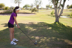 Female golfer ready to swing. Cute female golfer about to swing the ball with a club Stock Photos
