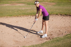Female golfer on a sand trap. Cute Hispanic female golfer trying to get her ball out of a sand trap Royalty Free Stock Photography