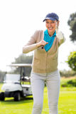Female golfer smiling at camera. On a sunny day at the golf course Royalty Free Stock Photo