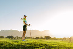Female golfer standing on golf course. Full length of caucasian female golfer standing on golf course. Woman playing golf on field on a sunny day Royalty Free Stock Image