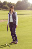 Female golfer standing on green. Attractive female golfer standing on the green with her putter, looking away with concentration to the next strike Stock Photography