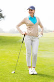 Female golfer standing with hand on hip Royalty Free Stock Image