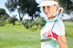Female golfer standing holding her club smiling at camera Royalty Free Stock Photography