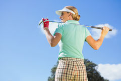 Female golfer standing holding her club Royalty Free Stock Image