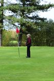Female golfer standing next to putting flag Stock Photos