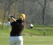 Female Golfer taken from behind. Female college golfer swings fairway wood. Taken from behind on follow through royalty free stock photos