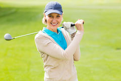 Female golfer taking a shot and smiling at camera Royalty Free Stock Image