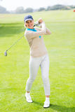 Female golfer taking a shot and smiling at camera Royalty Free Stock Photos