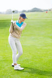 Female golfer taking a shot Royalty Free Stock Image