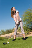 Female Golfer Teeing Off. Low angle view of a smiling female golfer teeing off against blue sky royalty free stock photo