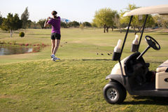 Female golfer teeing off Royalty Free Stock Photography