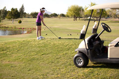Female golfer about to swing Stock Image