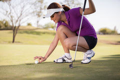 Female golfer trying to cheat Stock Image