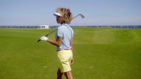 Female golfer walking down a fairway stock video footage