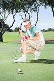 Female golfer watching her ball on putting green Stock Photos