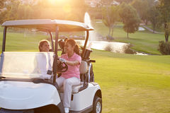 Female Golfers Driving Buggy Along Fairway Of Golf Course Stock Photos