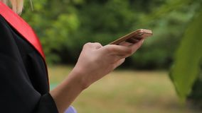 Female graduate checking messages on smartphone, using mobile applications. Stock footage stock video footage