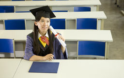 A female graduate in classroom Stock Image
