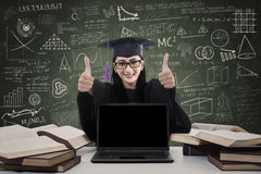 Female graduate giving thumbs up with copy space Royalty Free Stock Photography