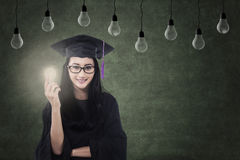 Female graduate holding lit bulb under lamps Stock Photos