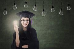 Female graduate holding lit bulb under lamps Stock Photos