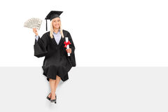 Female graduate holding money seated on a panel Stock Photo