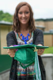 Female graduate holds her graduation cap out. Female graduate holds her graduate in front of her.  Hat has green and white tassle with 2015 Stock Image