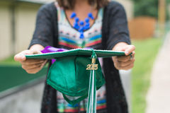 Female graduate holds at out to camera 2015. A female graduate proudly holds her graduate hat in front of her.  Green and white tassle has 2015 Royalty Free Stock Photography