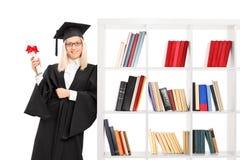 Female graduate leaning on a bookshelf Royalty Free Stock Photos
