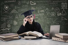 Female graduate learning with laptop Stock Photography