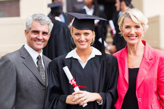 Female graduate parents. Smiling young female graduate with parents at graduation ceremony Royalty Free Stock Image
