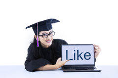 Female graduate pointing at like on laptop Royalty Free Stock Photos