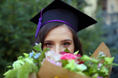 Female graduate. Portrait of a female graduate with flowers bouquet Royalty Free Stock Photography