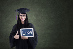 Female graduate showing like on e-tablet Stock Photos