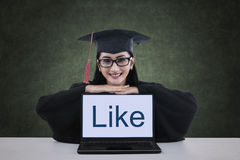 A female graduate showing like on laptop screen Royalty Free Stock Photography