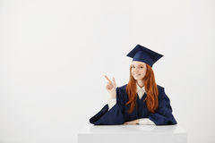Female graduate smiling pointing finger in side sitting over white background. Copy space. Stock Images