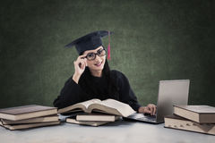Female graduate studying with books and laptop Royalty Free Stock Photography
