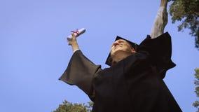Female graduate throwing graduation cap in the air