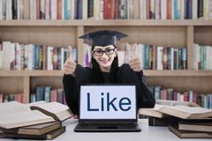 Female graduate thumbs up in library Royalty Free Stock Image