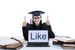 Female graduate thumbs up with like on laptop Stock Photo