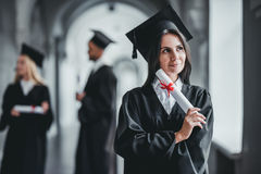 Female graduate in university. Happy female student graduate is standing in university hall in mantle with diploma in hand. Dreaming about future success royalty free stock image