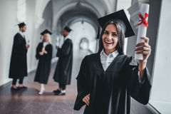 Female graduate in university. Happy female student graduate is standing in university hall in mantle with diploma in hand, smiling and looking at the camera royalty free stock photos