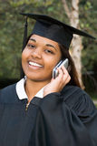 Female graduate using a cellular telephone Royalty Free Stock Photography